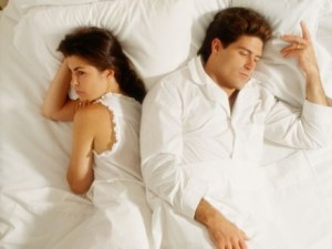 Disagreeing couple lying in bed